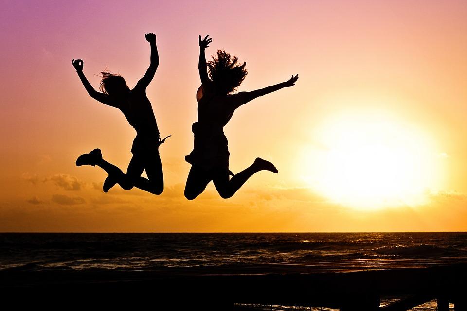 浜辺で成功のジャンプをする二人